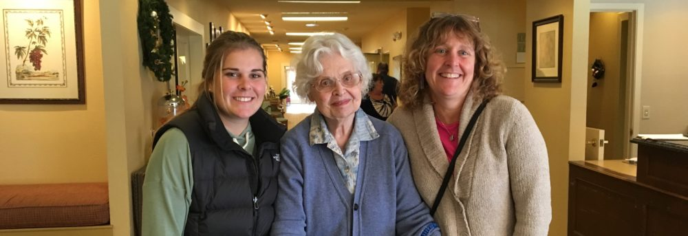 Molly, Barbara, Margo. Molly is wearing an olive green long-sleeve shirt and a black down vest with her long hair pulled back in a pony tail. Barbara is wearing a light blue collared shirt and violet blue sweater. She has short white hair and is using a walker. Margo is wearing black pants and a beige sweater with her purse across her body