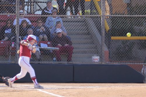 Molly at the plate for Stanford hitting a double. She's finishing her swing and the ball is in the air in the right side of the photos. She's wearing white pants and a Cardinal red top with a red helmet