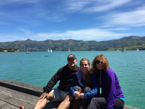 Dan, Margo, Molly in New Zealand after scattering Jimmy's ashes. Dan is wearing khaki shorts, a black jacket and a LIVESTRONG baseball cap. Molly has dark gray workout pants and a navy windbreaker on, and she's wearing her hair in a ponytail. Margo is wearing black pants, sunglasses and a purple jacket