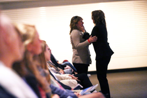 Regina comforting Margo at Jimmy's celebration of life. Regina is wearing a black blazer and black pants and has brown wavy hair. Margo is wearing a tan sweater with buttons and black pants. She has light brown wavy hair.