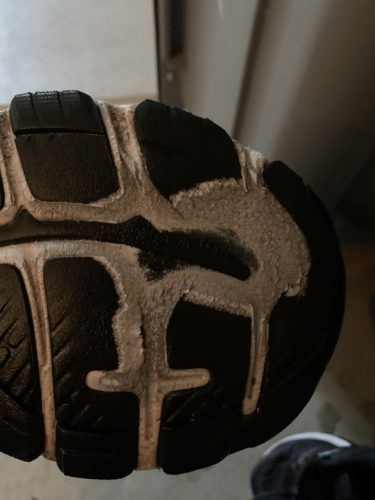 Bottom of an Asics running shoes. In places, the black tread is worn completely away